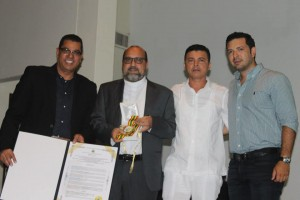 Rev. Milciádes Pua holds the medal received, along with municipal authorities and the Rector of the American College, Adriano Portillo (UniReformada)